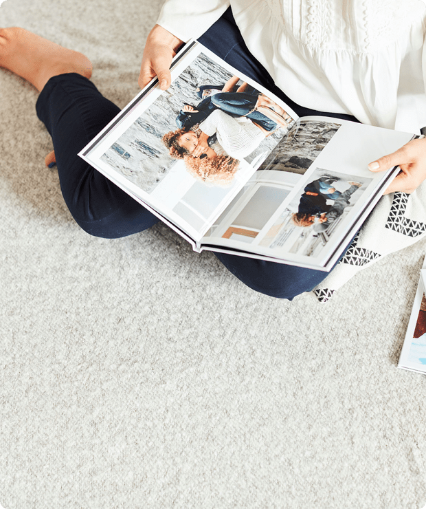 woman sitting on carpet holding a photobook open